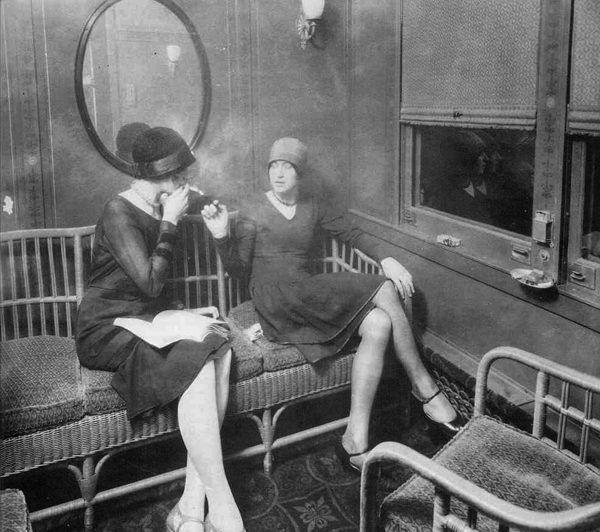 Flapper women smoking in a train car
