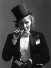 Marlene Dietrich - dressed in a top hat and tuxedo, smoking a cigarette